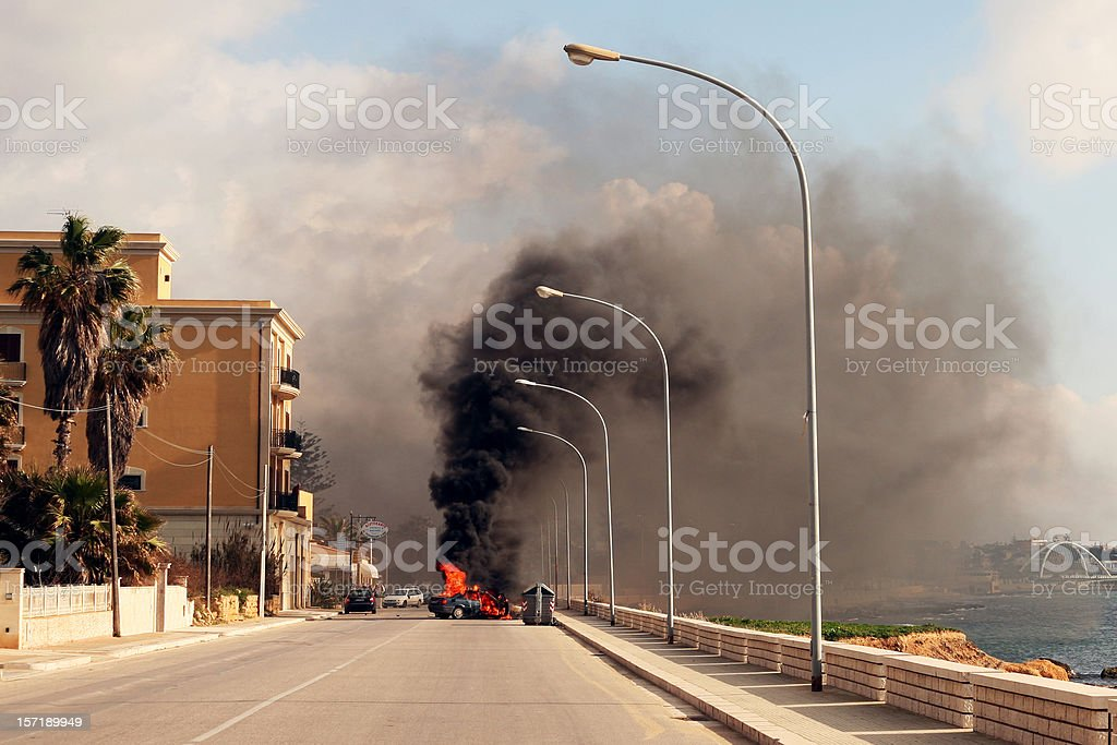 Burning car in the street of sicilian town. stock photo