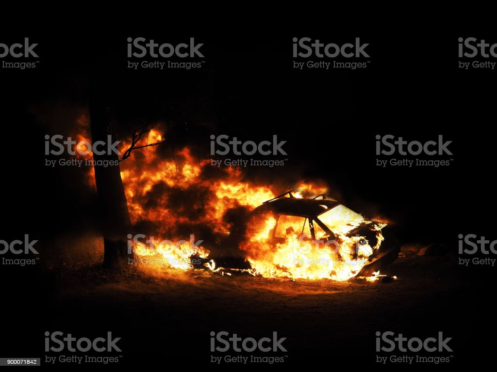 Burning car. Night. Consequences of the collision with a tree. Car on fire isolated on black background stock photo