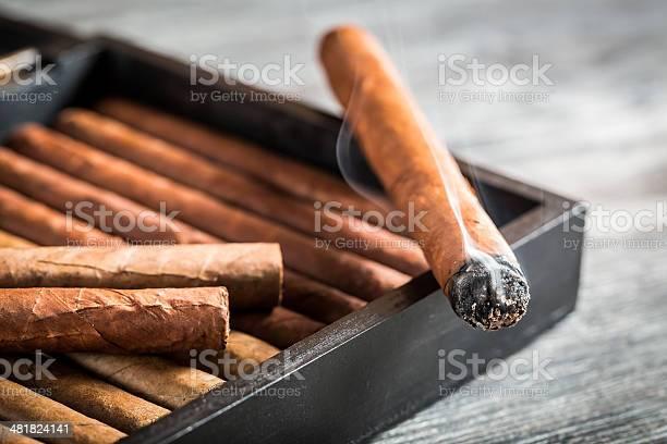 Burning cigar with smoke on wooden humidor.