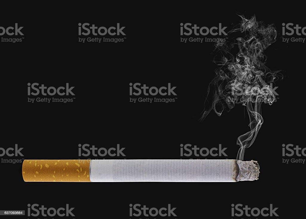 Burning cigarette, black background stock photo
