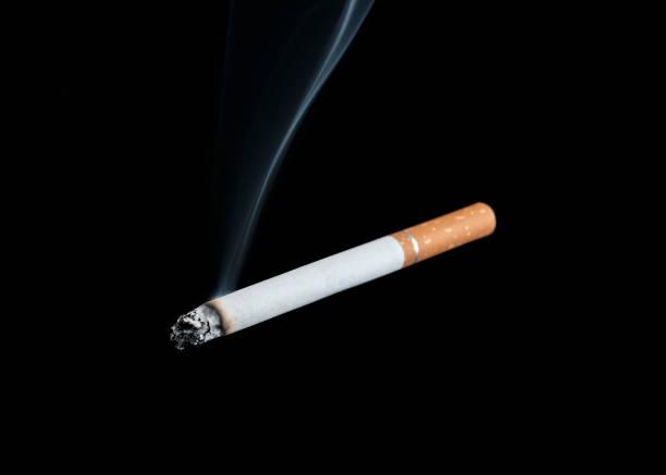 Burning Cigarette Isolated On A Black Background stock photo