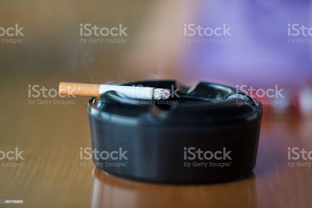 Burning cigarette smoking on black ashtray stock photo