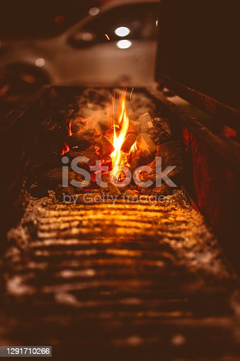 Vertical image of burning flame in a charcoal barbeque grill on a cold winter night.