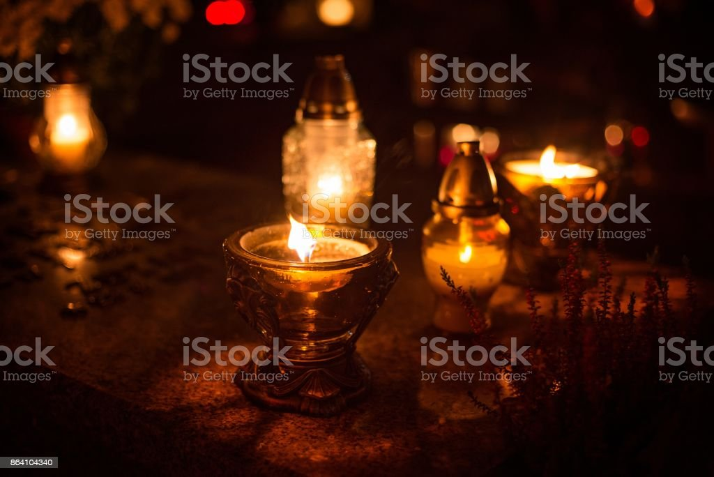 Burning colourful candles on cemetery at night. royalty-free stock photo