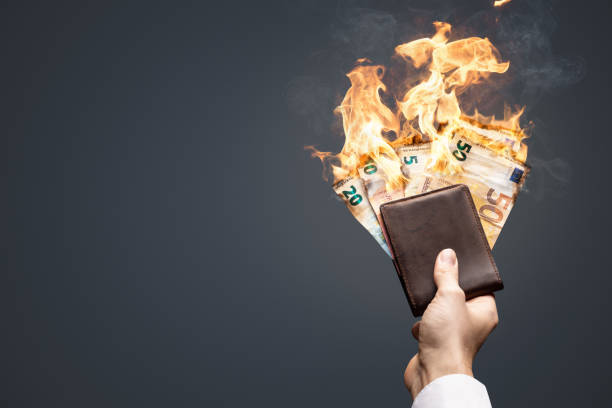 Burning Euro bills in a wallet Euro bills are burning with bright flames. They are held in a wallet by one hand. depreciation stock pictures, royalty-free photos & images