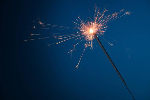 Burning festive Christmas sparkler on blue background