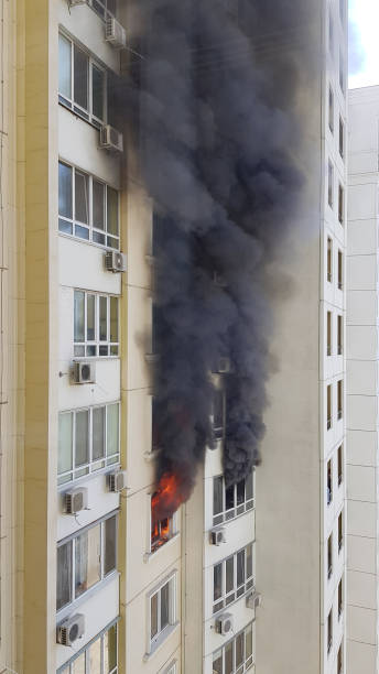 Burning fire and blurry black smoke due to arson in building stock photo