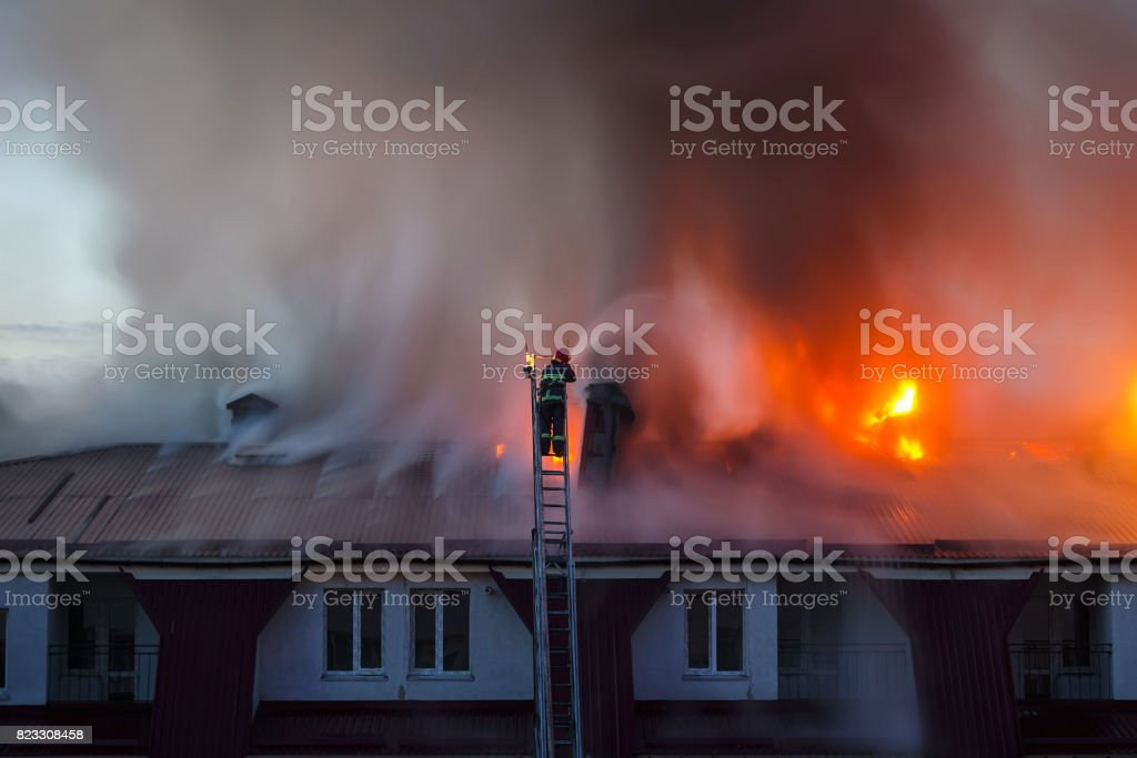 Burning fire flame with smoke on the apartment house roof in the city, firefighter or fireman on the ladder extinguishes fire stock photo