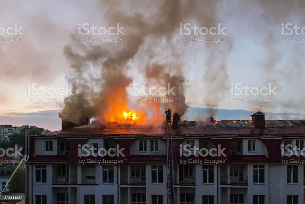 Burning fire flame with smoke on the apartment house roof in the city, firefighter on the ladder extinguishes fire stock photo