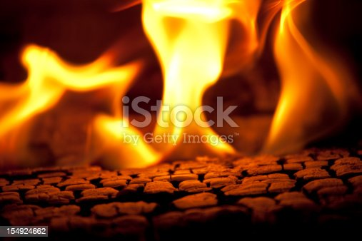 Hot coals and flames emitting from a hot burning fire.