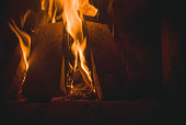 Burning red and yellow fire place on dark background.