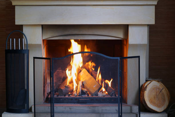 Burning Fireplace in winter time. A warm fire in the stone fireplace on a cold night. Warm cozy fireplace with real wood burning in it. Cozy winter concept. Christmas and travel. Christmas backgrounds. Magic burning fireplace. log fire stock pictures, royalty-free photos & images