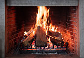 Fireplace, cozy warm fireside. Fire burning, logs flaming, firebricks background. Relaxation at home winter holiday christmas time
