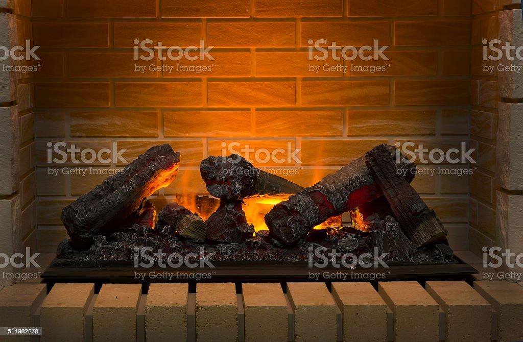 burning firewood in brick fireplace stock photo