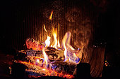 Burning firewood in fireplace in the house. Cozy home interior, warm place. Home backgrounds