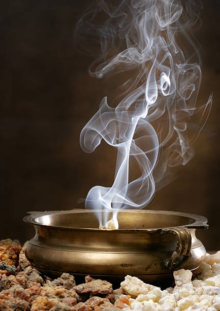 Burning Frankincense and Myhrr Frankincense and Myhrr burn with curling smoke patterns in an antique brass bowl. Chunks of Frankincense and Myhrr are in the foreground. incense stock pictures, royalty-free photos & images