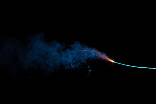 Burning fuse with sparks and blue smoke isolated on black background stock photo