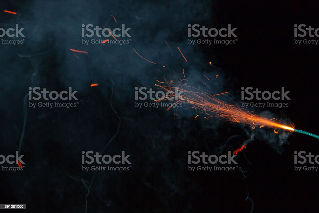 Burning fuse with sparks and grey smoke on black background stock photo