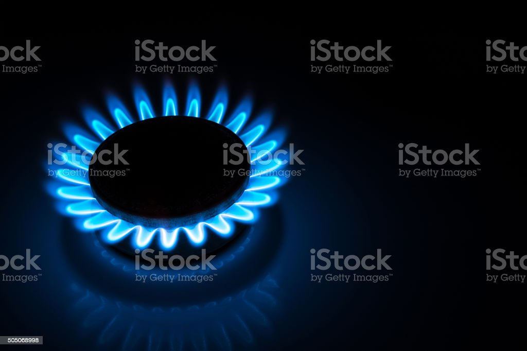 burning gas stove hob blue flames  in the dark stock photo
