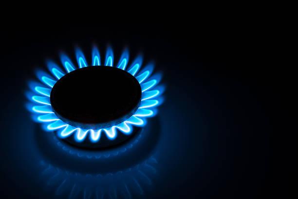 gas de combustión estufa hob azul llamas en la oscuridad - foto de stock