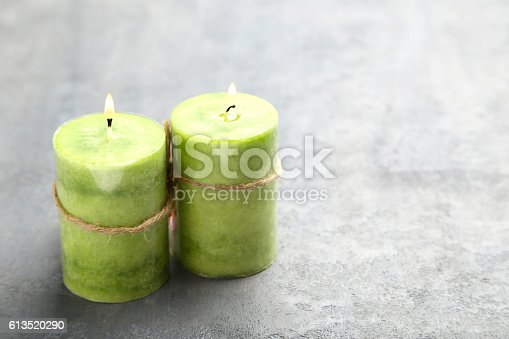 Burning green candles on grey table