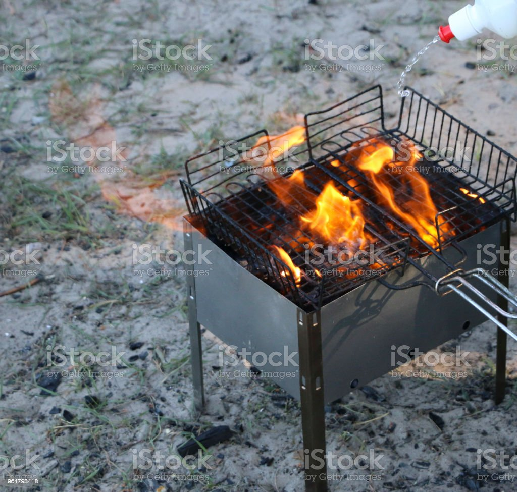 burning grill. on brazier with hot coals is a grill. coals are watered with a special liquid for strong combustion. royalty-free stock photo