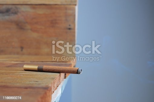 Burning handmade luxury Cuban cigar on an old wooden background with copyspace