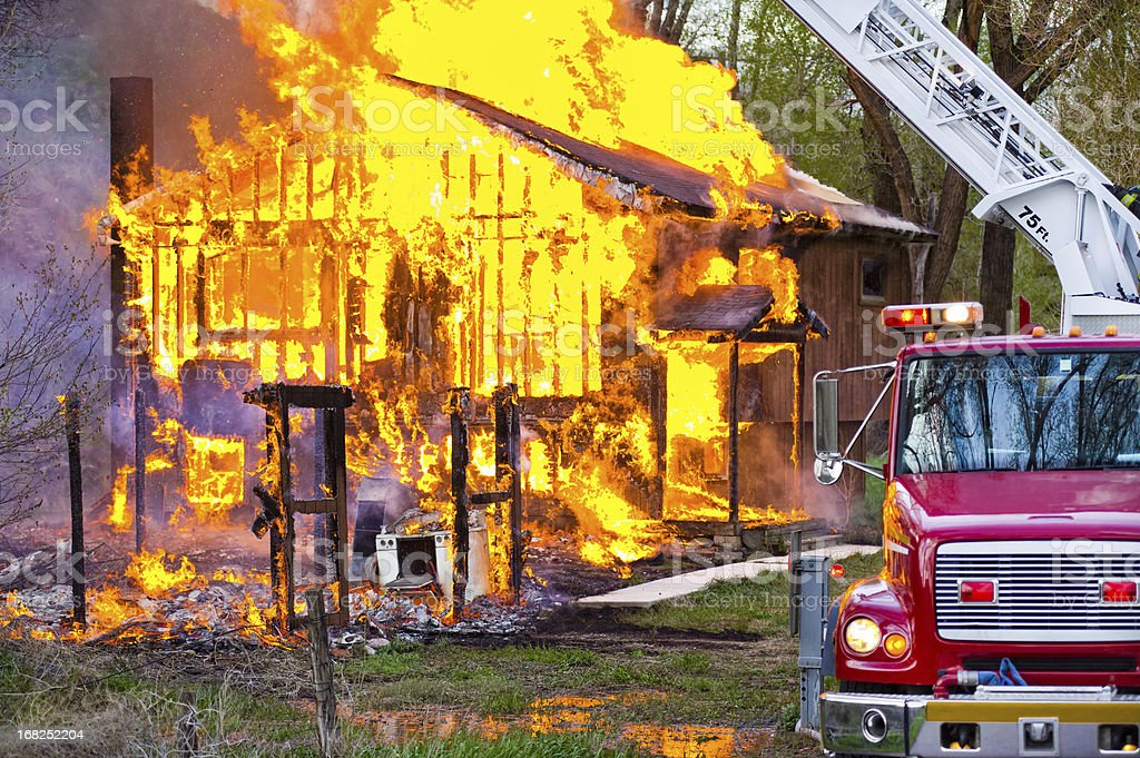 Burning House Fire with Emergency Services Truck stock photo