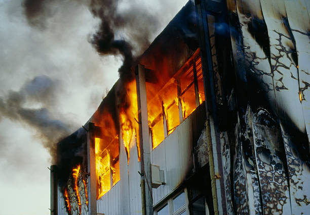 Burning house upper floor and and ascending black smoke stock photo