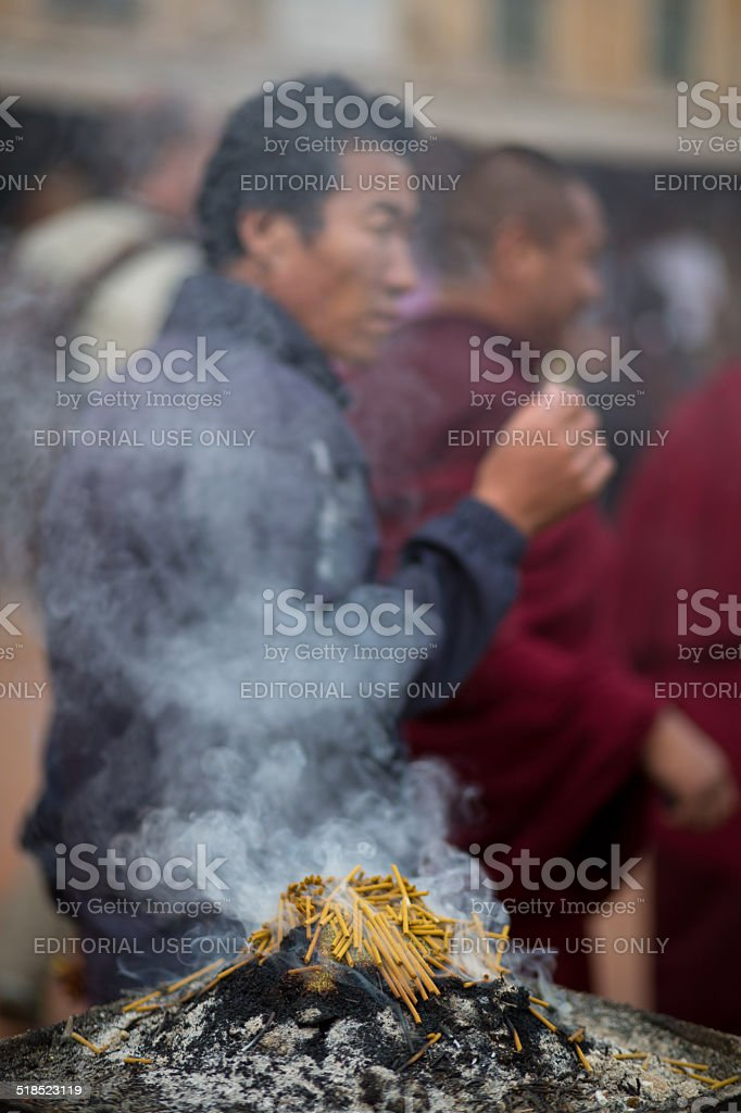Burning incence and unidentified praying blurred man stock photo