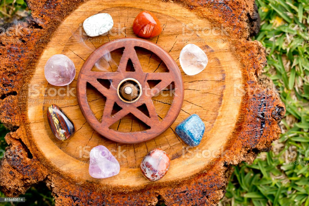 Burning incense cone  in wooden pentacle incense holder on natural cut tree log with variety of crystals stock photo