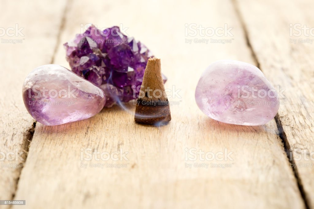 Burning incense cone with amethyst crystals with wafting smoke on wooden background stock photo