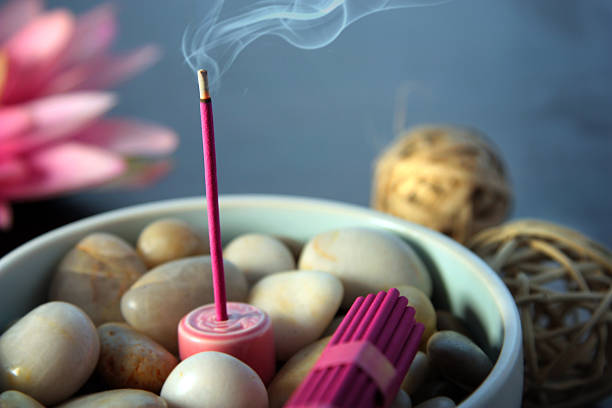 Burning Incense Pink incense stick smouldering in a bowl of river pebbles.  Themes of relaxation, aromatherapy and eastern rituals. incense stock pictures, royalty-free photos & images