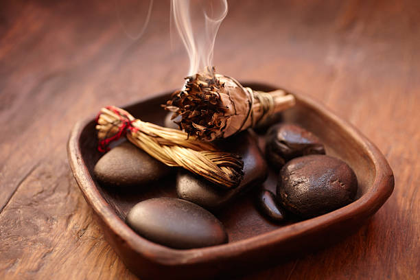 burning incense sage stick and pebbles - ceremonie stockfoto's en -beelden