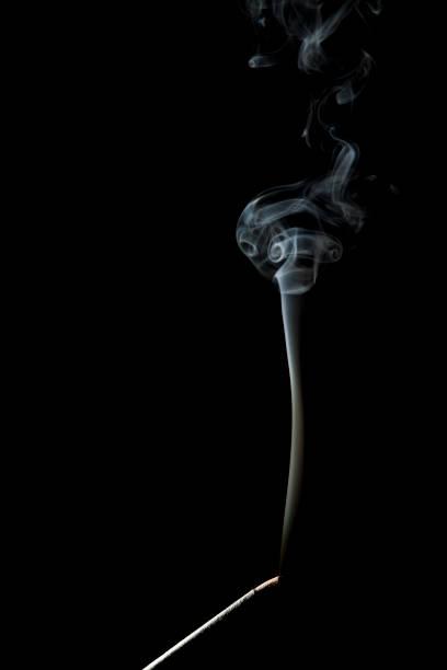 Burning incense stick on a black background stock photo