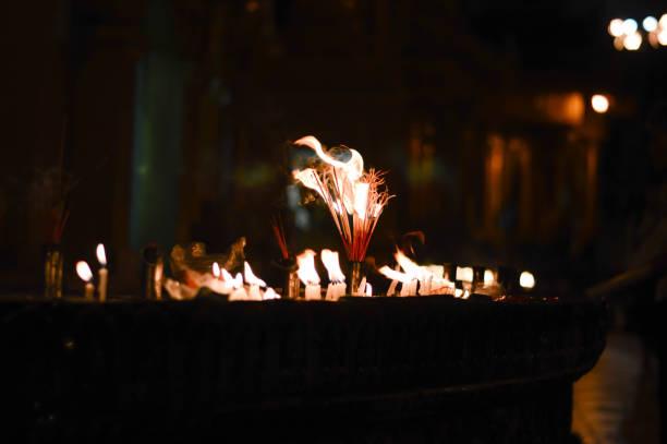 weihrauch-sticks und kerzen licht die dunkelheit. - kult stock-fotos und bilder