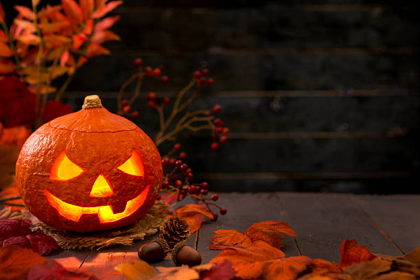 Burning Jack O'Lantern on a rustic table with autumn decorations stock photo