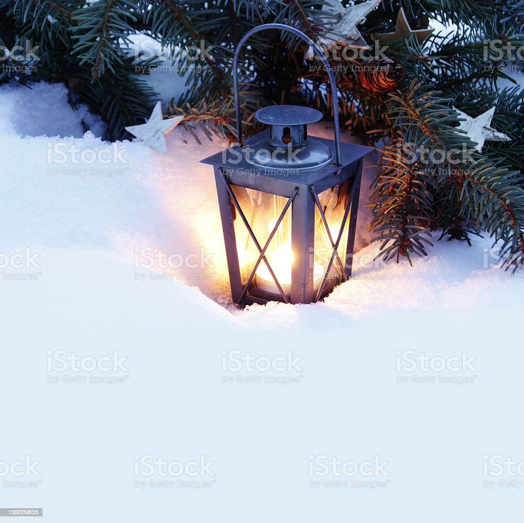 Burning lantern in snow by Christmas tree with star decor royalty-free stock photo