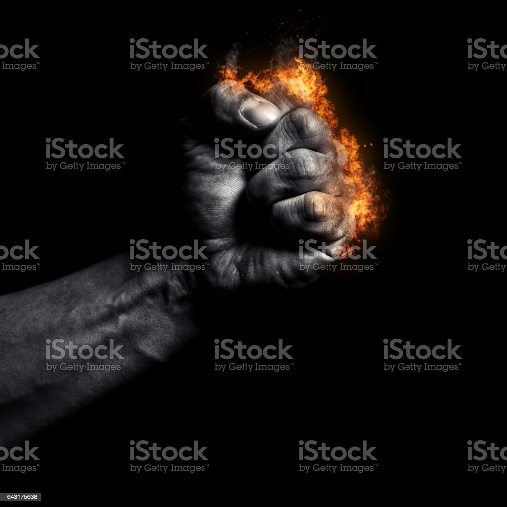 Burning man's clenched fist on a black background stock photo