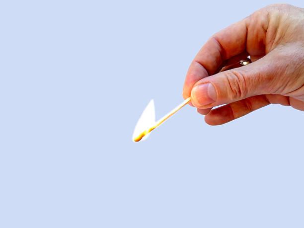 burning match held by 2 fingers isolated on light background - hand tänder ett ljus bildbanksfoton och bilder
