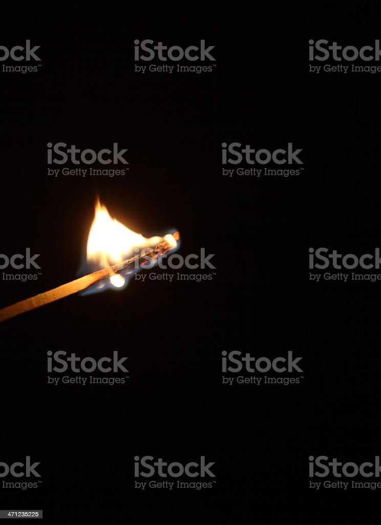burning matchstick on black stock photo