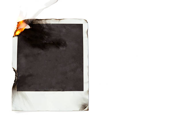 Burning memories: Blank Polaroid Photo on Fire stock photo