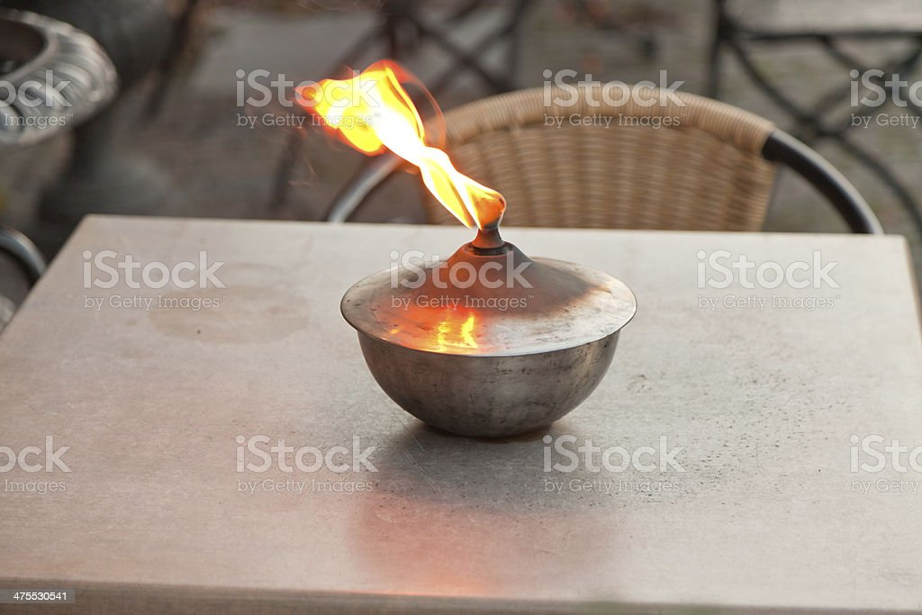 Burning oil lamp on table outdoors. stock photo