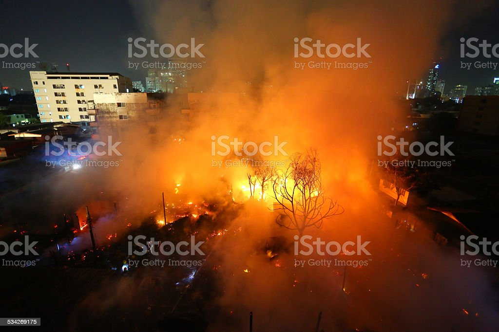 Burning old abandoned house in the city at dusk stock photo