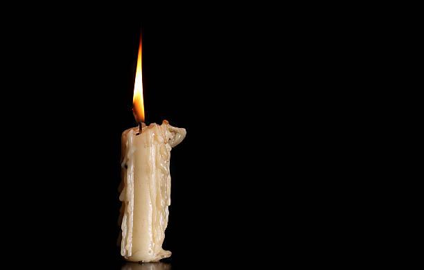 Burning Old Candle on Black Background. stock photo