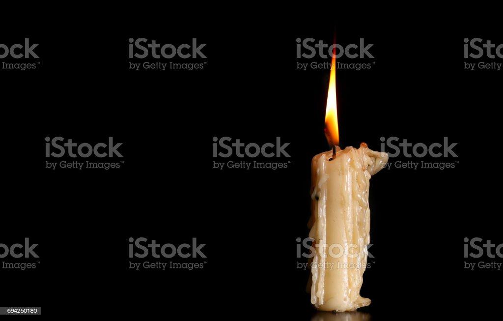 Burning Old Candle on Black Background stock photo