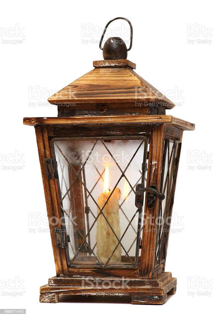 burning old candle vintage wooden candlestick. Isolated on white background. stock photo