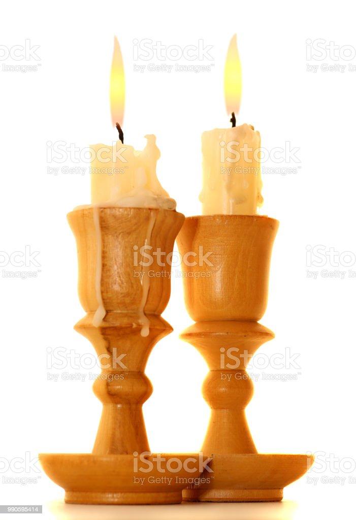 burning old candle vintage wooden candlestick. Isolated on white background stock photo