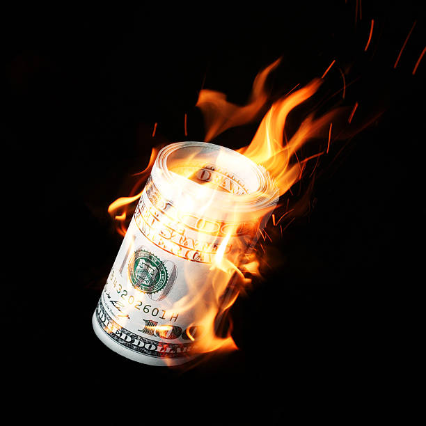 Burning one hundred dollar bills rolled Burning one hundred dollar bills rolled black background money to burn stock pictures, royalty-free photos & images
