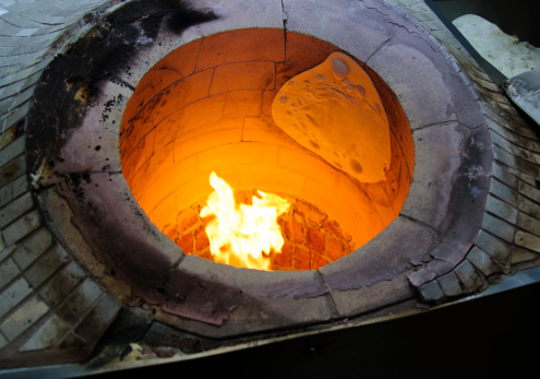 baking lavash pita bread in burning stone oven in a Turkish bakery